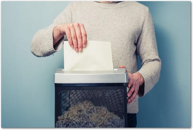 紙をシュレッダーにかける男性