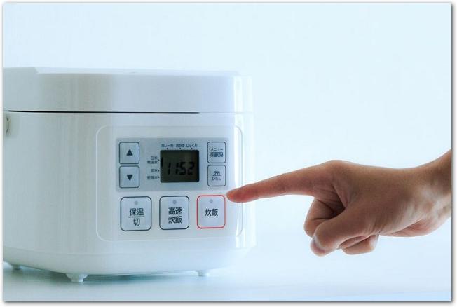 炊飯器とボタンを押そうとしている人の手