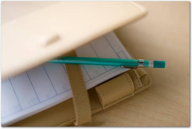 白いカバーがついたシステム手帳とペン