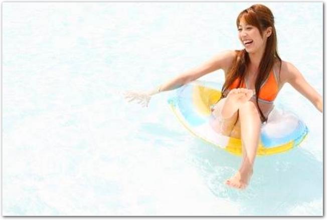 浮き輪にのってはしゃぐ若い女性